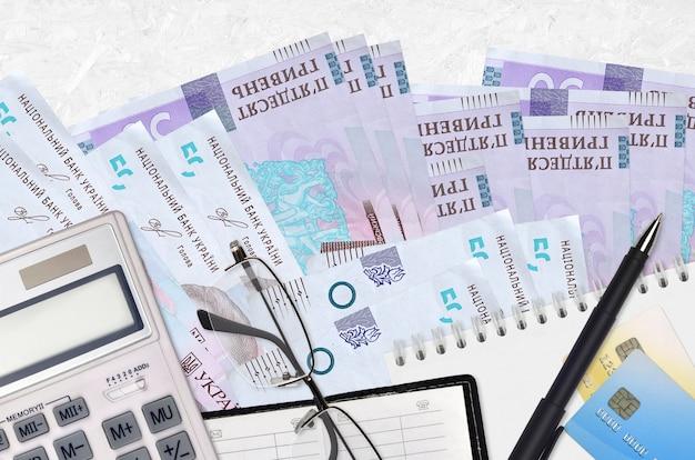 50 ukrainische griwna rechnungen und taschenrechner mit brille und stift