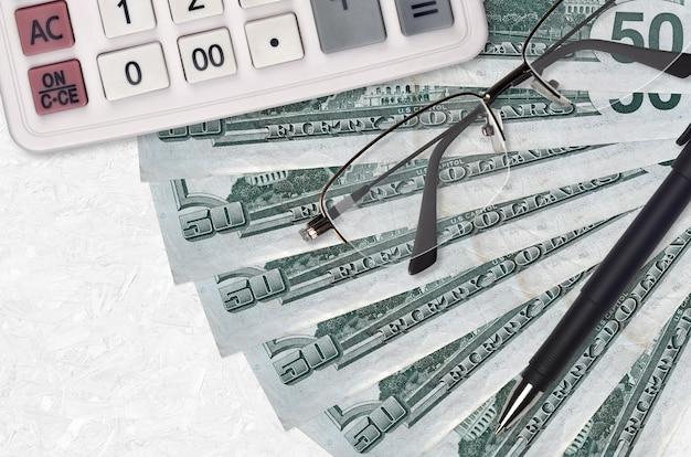 50 us-dollar-scheine fan und taschenrechner mit brille und stift. geschäftskredit- oder steuerzahlungssaisonkonzept.