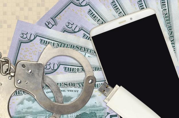 50 us-dollar-scheine und smartphone mit polizeihandschellen. konzept von hacker-phishing-angriffen, illegalem betrug oder online-spyware-softdistribution