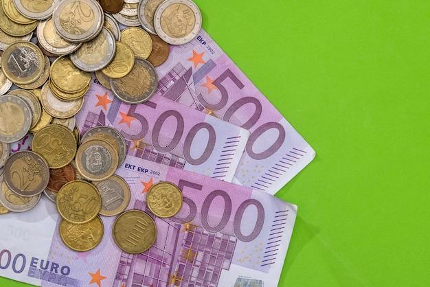 500 euro banknoten mit münze auf grün