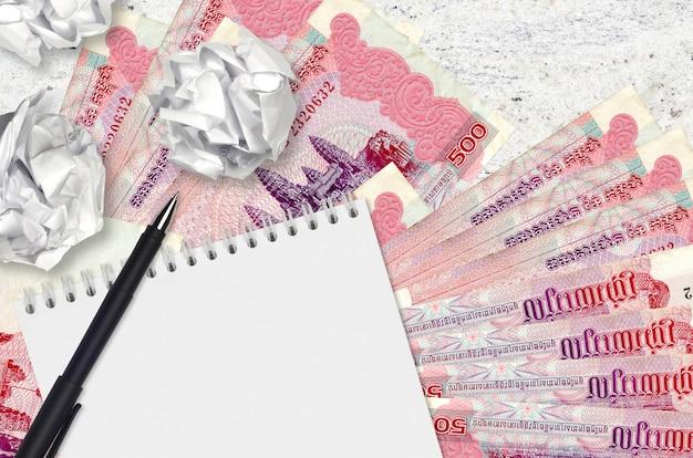 500 kambodschanische geldscheine und zerknitterte papierkugeln mit leerem notizblock. schlechte ideen oder weniger inspirationskonzept. ideen für investitionen suchen