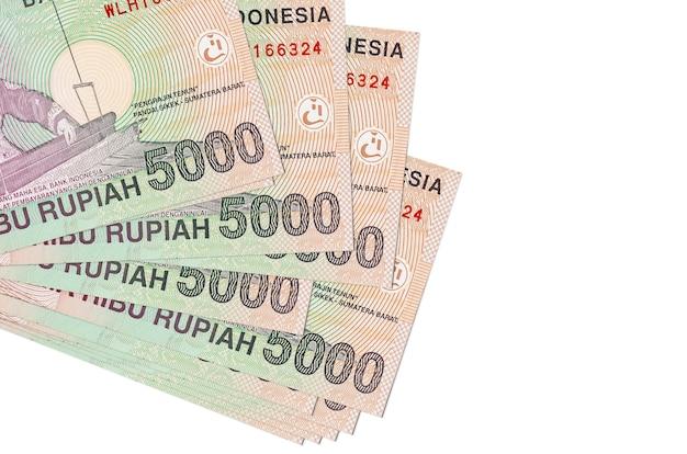 5000 indonesische rupiah-scheine liegen in kleinen bündeln oder packungen, die auf weiß isoliert sind. geschäfts- und geldwechselkonzept