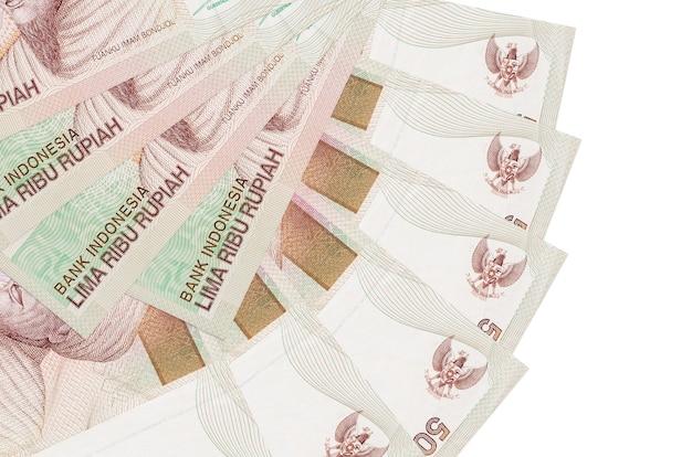 5000 indonesische rupiah-scheine liegen isoliert auf weißer wand mit in fächerform gestapeltem kopierraum in nahaufnahme. finanztransaktionskonzept