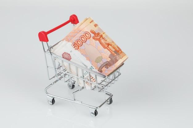 5000 russische rubelbanknoten im einkaufswagen auf grauer wand, konzept