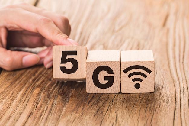 5g (5th generation) netzwerktechnologie zukunft global. holzwürfel mit der hand drehen und die nummer 4g auf 5g ändern
