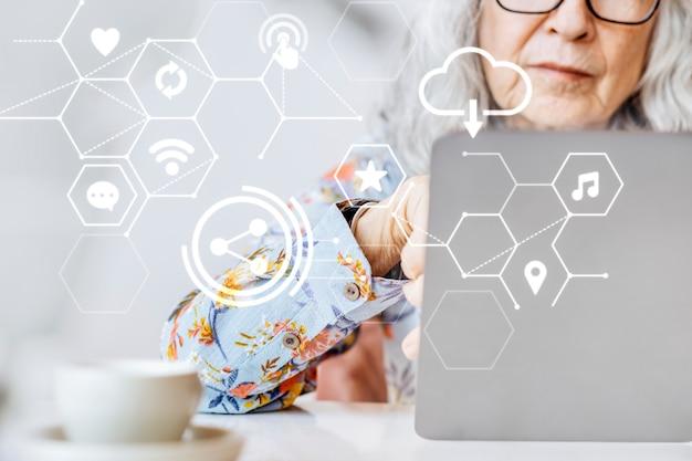 5g globale verbindung mit einer älteren frau, die an einem laptop-smart-technologie-remix arbeitet