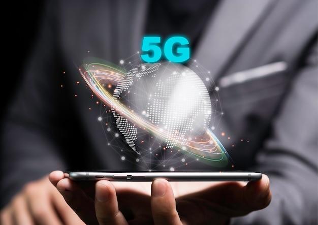 5g und internet der dinge oder iot-konzept, geschäftsmann hält smartphone mit 5g auf welt