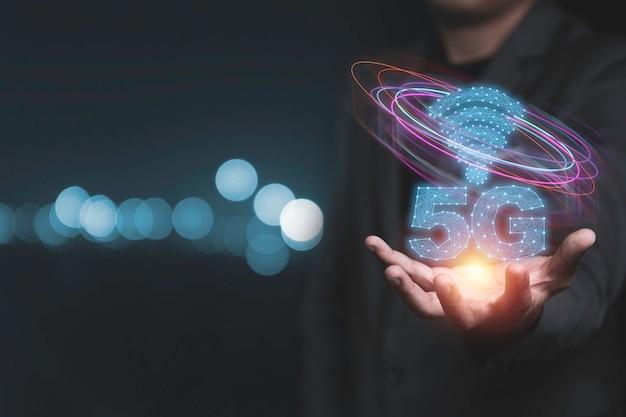 5g und internet der dinge oder iot-konzept, hand halten smartphone mit virtuellem 5g-signal. iot ist eine hochtechnologie, die jedes gerät über das 5g-hochgeschwindigkeitsinternet verbindet und steuert.