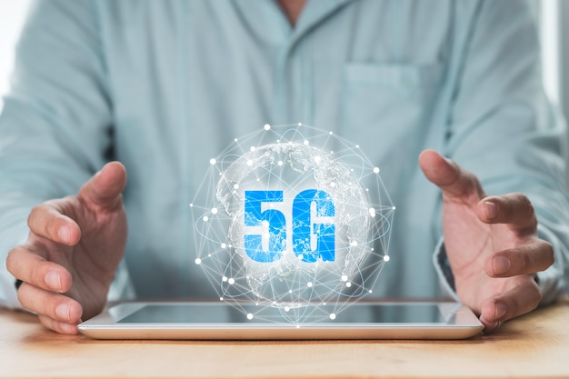 5g und internet of ding oder iot-konzept, geschäftsmann schützt virtuelles 5g globales netzwerk auf tablet.