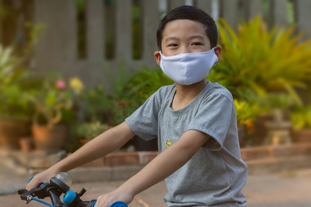 6-7 jahre alter asiatischer junge mit schwarzen haaren trägt eine weiße gesichtsschutzmaske und bereitet sich darauf vor, auf unscharfem hintergrund im freien fahrrad zu fahren. bild für pm 2.5 mikrostaubverschmutzung oder covid-19-geschütztes konzept.