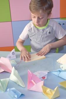 6-jähriger junge macht origami-flugzeuge und frösche während der quarantäne covid-19, selbstisolation, online-bildungskonzept, homeschooling. kind zu hause, kindergarten geschlossen, kinderkunst.