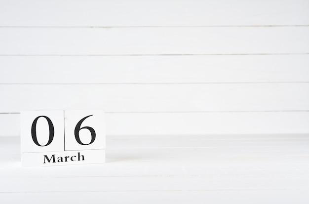 6. märz, tag 6 des monats, geburtstag, jahrestag, holzblockkalender auf weißem hölzernem hintergrund mit kopienraum für text.