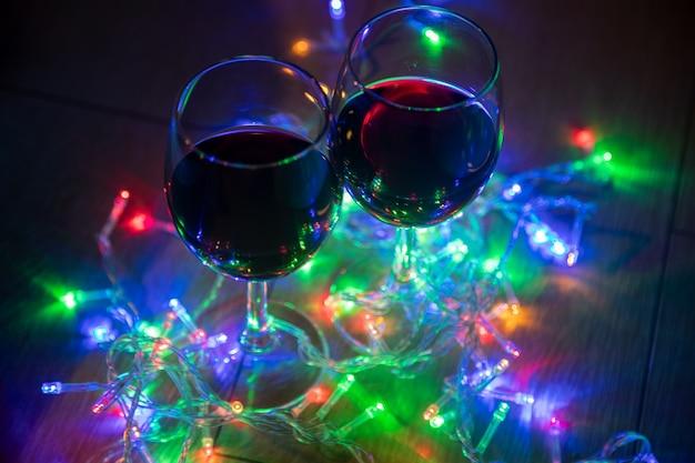 7/8 hand hält weinglas über bunt beleuchtete weihnachtsbeleuchtung in dunkelkammer