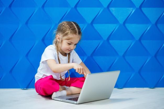7 jahre altes mädchen in einem weißen t-shirt sitzt mit einem laptop auf dem boden und drückt die tasten