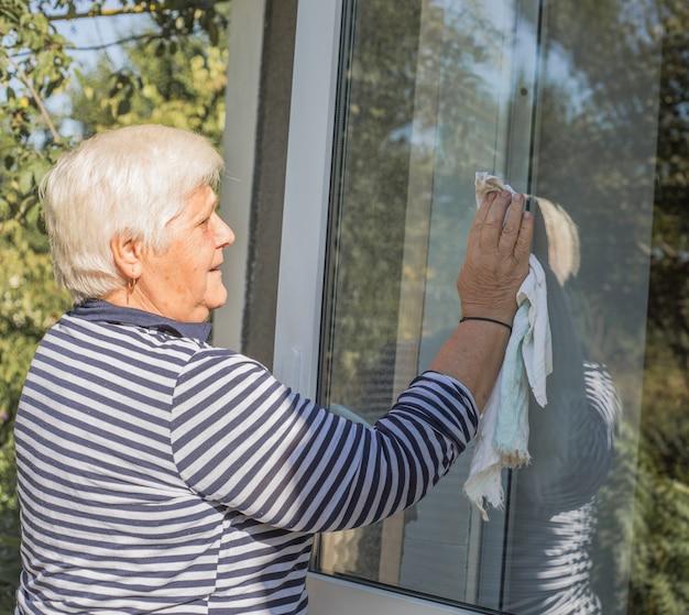 70-jährige frau reinigt fenster von flecken mit lappen und sprühreiniger. kaukasische ältere frau putzt haus und erledigt haushaltsarbeiten.