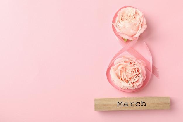 8 aus band, holzblock mit text märz und rosen auf rosa hintergrund