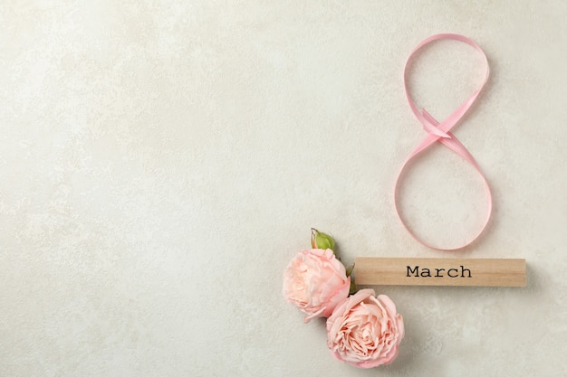 8 aus band, holzblock mit text märz und rosen auf weißem strukturiertem hintergrund