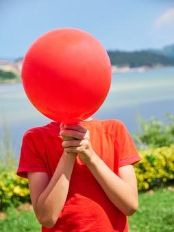 8-jähriger junge versteckt sein gesicht hinter einem roten ballon, isoliert, im garten