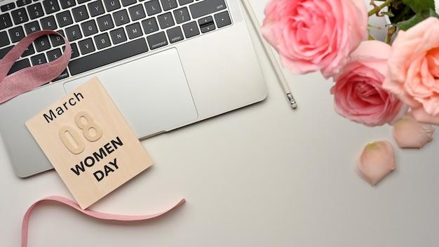 8. märz frauentag am arbeitsplatz mit laptop, bleistift und rosa blumen auf weißem tisch