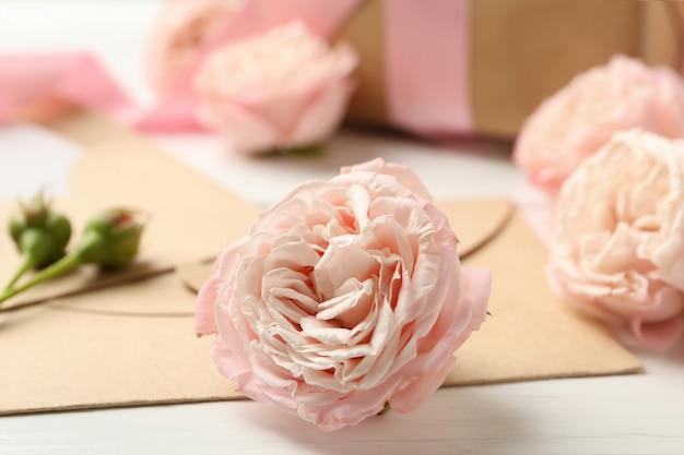 8. märz konzept mit rosen und umschlägen auf weißem holzhintergrund
