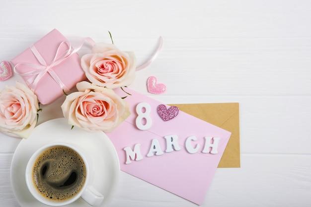 8. märz text auf karton mit rosa dekorationen und tasse kaffee