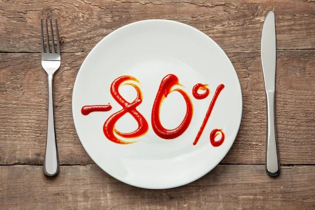 80% rabatt auf essen. verkauf von lebensmitteln. teller mit der aufschrift ketchup und gabel mit messer auf holztisch.