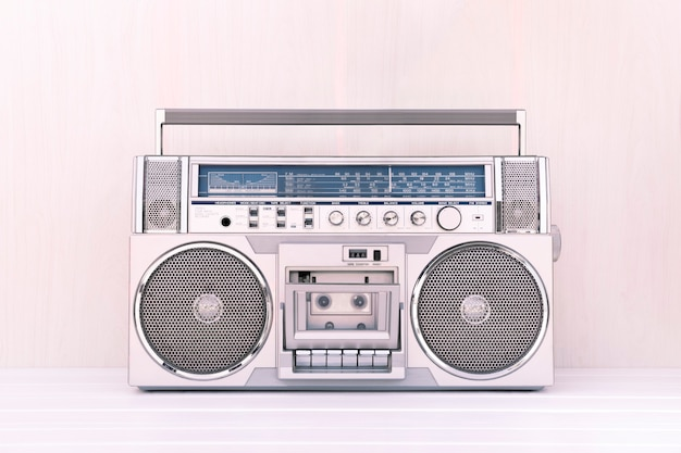 80er jahre retro-kassettenradio in silberner farbe auf hellem holzhintergrund. musikkonzept spielen.