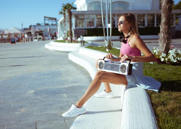 80er jahre stil bild einer jungen attraktiven frau mit boombox-audio-tonbandgerät an einem sonnigen tag im freien