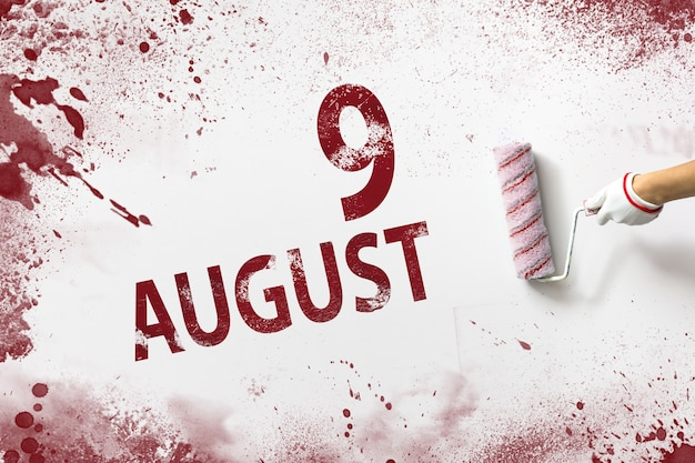 9. august. tag 9 des monats, kalenderdatum. die hand hält eine rolle mit roter farbe und schreibt ein kalenderdatum auf einen weißen hintergrund. sommermonat, tag des jahreskonzepts.