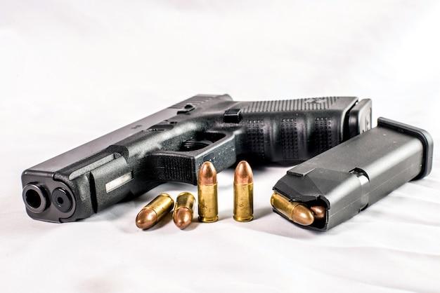 9 millimeter-pistolengewehr und kugeln gestreut mit munition auf hölzernem hintergrund