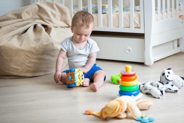9 monate altes baby spielt mit spielzeugauto und spielzeugturm