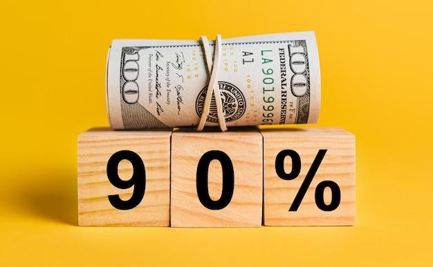 90 zinsen mit geld auf gelbem grund. das konzept von geschäft, finanzen, kredit, einkommen, ersparnissen, investitionen, austausch, steuern
