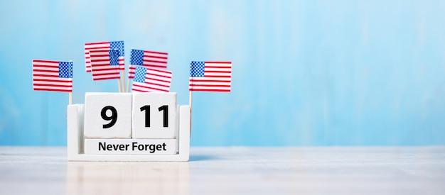 911 nie vergessen mit flagge der vereinigten staaten von amerika auf holzhintergrund.
