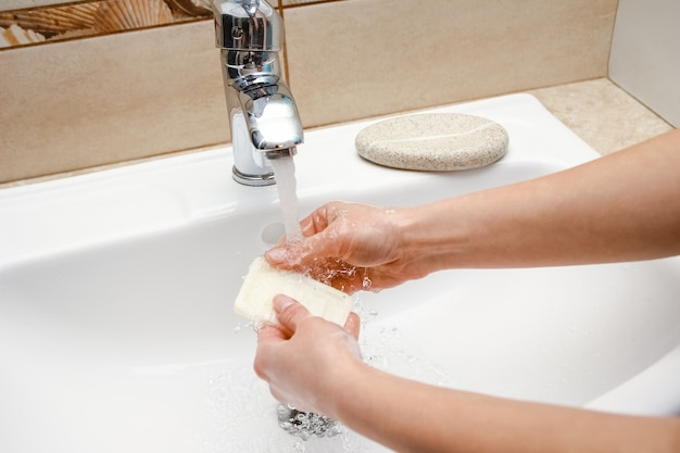 A hände mit seife werden unter wasserhahn mit wasser gewaschen. reinigen sie es von infektionen, schmutz und viren. zu hause oder im waschbüro des krankenhauses.