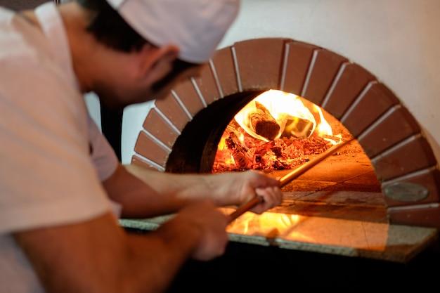 á¡hef bereitet pizza im traditionellen steinofen zu.