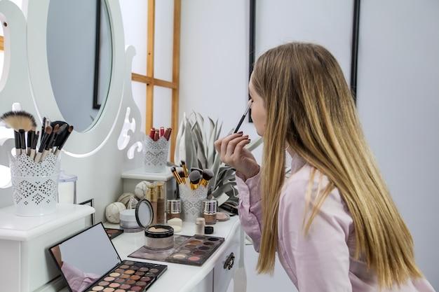 A sie schaut sich in den spiegel und macht ihr make-up