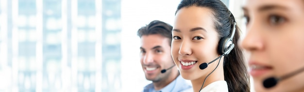 Aasian frau, die im kundenkontaktcenter im fahnenhintergrund arbeitet