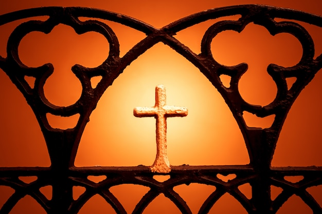 Abbildung eines kreuzes auf einem orangefarbenen hintergrund. christliches kreuz silhouette.