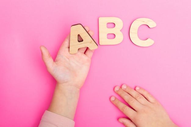 Abc-buchstaben in den kinderhänden auf rosa hintergrund