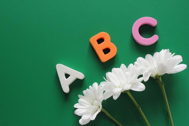 Abc - die ersten buchstaben des englischen alphabets und drei weiße chrysanthemen