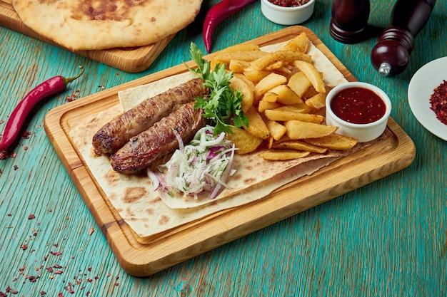 Abchasisch ist ein georgisches gericht aus einer mischung aus hackfleisch, das auf einem grill mit roter sauce und ofenkartoffeln gebraten wird. georgischer kebab