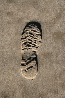 Abdruckschuh auf braunem sand-beschaffenheitsdruck des strandes