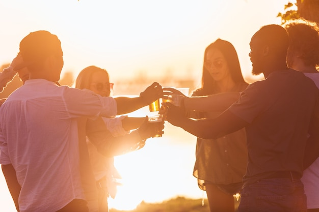 Abend. gruppe von freunden, die beim picknick am strand bei sonnenschein mit biergläsern klirren. lifestyle, freundschaft, spaß, wochenende und ruhekonzept. sieht fröhlich, fröhlich, feiernd, festlich aus.