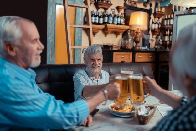 Abend in der kneipe. grauhaarige, fröhliche rentner verbringen den abend in der kneipe und trinken bier