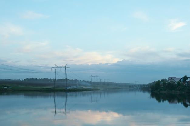 Abend neblige landschaft der landschaft. der fluss ist im nebel. drähte der elektrischen spannung.