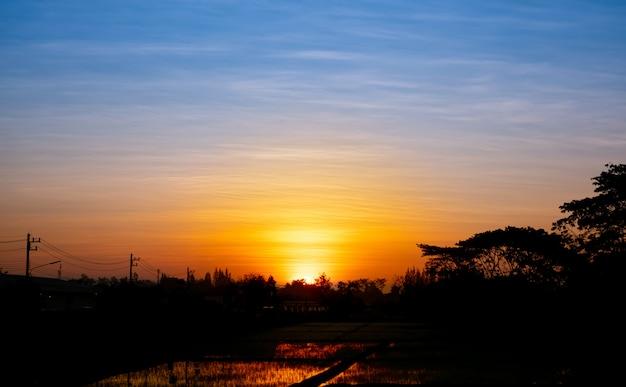 Abend sonnenuntergang über den feldern. die ländliche landschaft unter dem bunten himmel, warmer horizont.