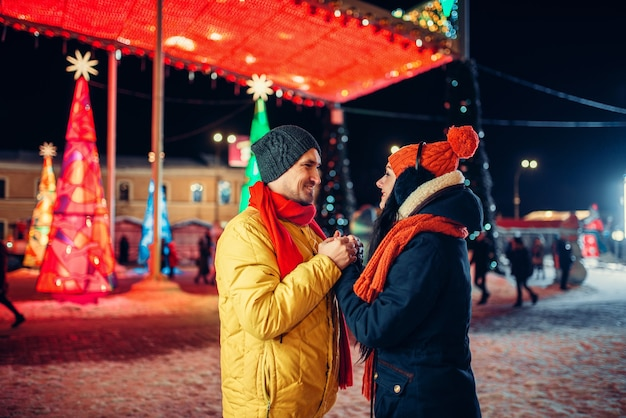 Abend winterspaziergang, liebespaar auf dem platz. mann und frau, die romantisches treffen auf stadtstraße mit lichtern haben