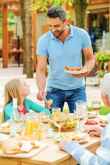 Abendessen an der frischen luft. junger mann legt gegrilltes hähnchen auf die teller, während seine familie am esstisch sitzt sitting