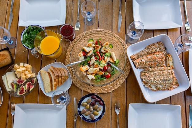 Abendessen auf der tischplatte ansicht gegrillter lachs zum abendessen mit salat abendessen für eine große gesellschaft