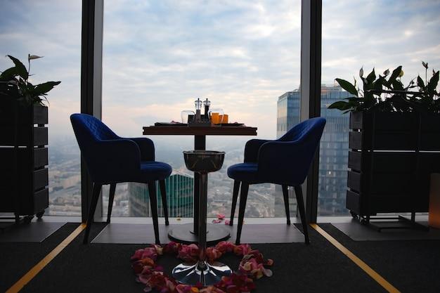 Abendessen bei sonnenuntergang mit blick auf das moskauer geschäftszentrum. abendessen im hintergrund der stadt. restaurant mit blick auf die innenstadt. romantisches ambiente, moskau, russland